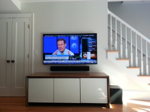 tv on wall over cabinet